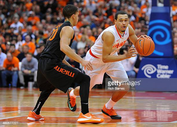 Tyler Ennis of the Syracuse Orange dribbles the ball up the court around the defense of Manu Lecomte of the Miami Hurricanes during the second half...