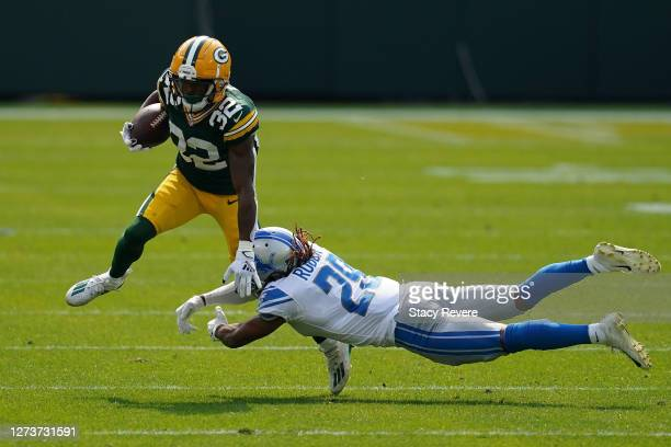 Tyler Ervin of the Green Bay Packers is tripped up by Darryl Roberts of the Detroit Lions during the second quarter at Lambeau Field on September 20...