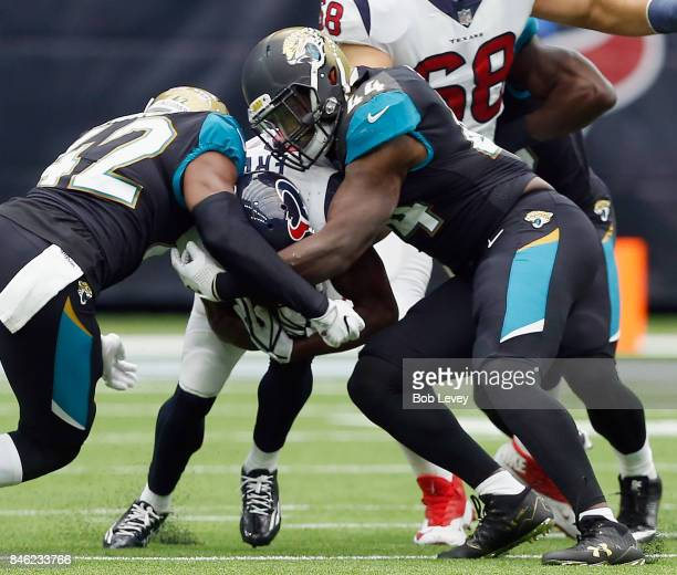 Tyler Ervin of the Houston Texans is tackled by Myles Jack of the Jacksonville Jaguars and Barry Church at NRG Stadium on September 10 2017 in...