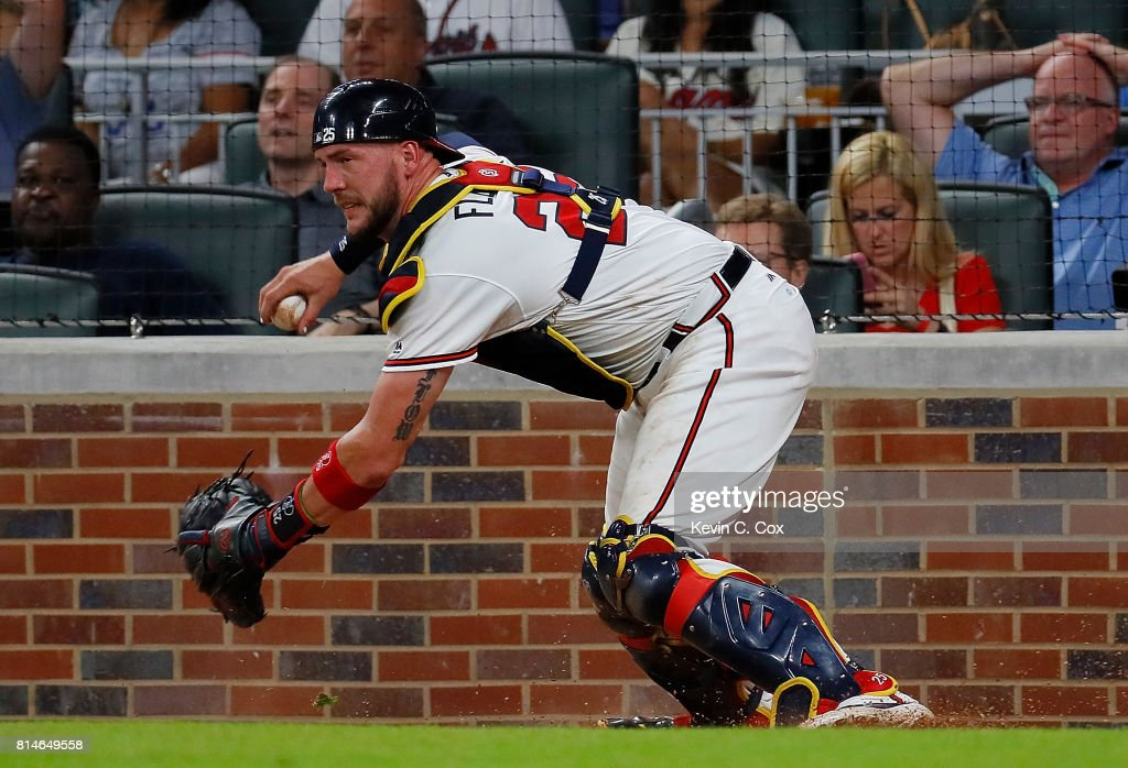 Tyler Flowers #25 of the Atlanta Braves chases down a wild pitch by Jose Ramirez #52 that allowed Chris Owings #16 of the Arizona Diamondbacks to score in the seventh inning at SunTrust Park on July 14, 2017 in Atlanta, Georgia.