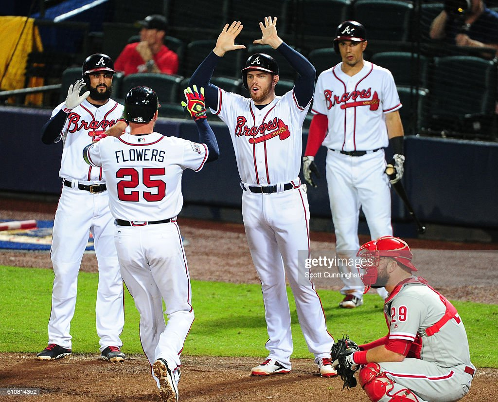 Tyler Flowers #25 of the Atlanta Braves is congratulated by Nick Markakis #22, Freddie Freeman #5, and Jace Peterson #8 (L-R) after hitting a sixth inning three-run home run against the Philadelphia Phillies at Turner Field on September 27, 2016 in Atlanta, Georgia.