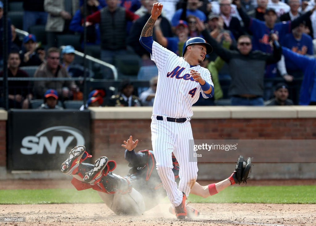 Tyler Flowers #25 of the Atlanta Braves tires to make the tag as Wilmer Flores #4 of the New York Mets slides home safely in the seventh inning during Opening Day on April 3, 2017 at Citi Field in the Flushing neighborhood of the Queens borough of New York City.