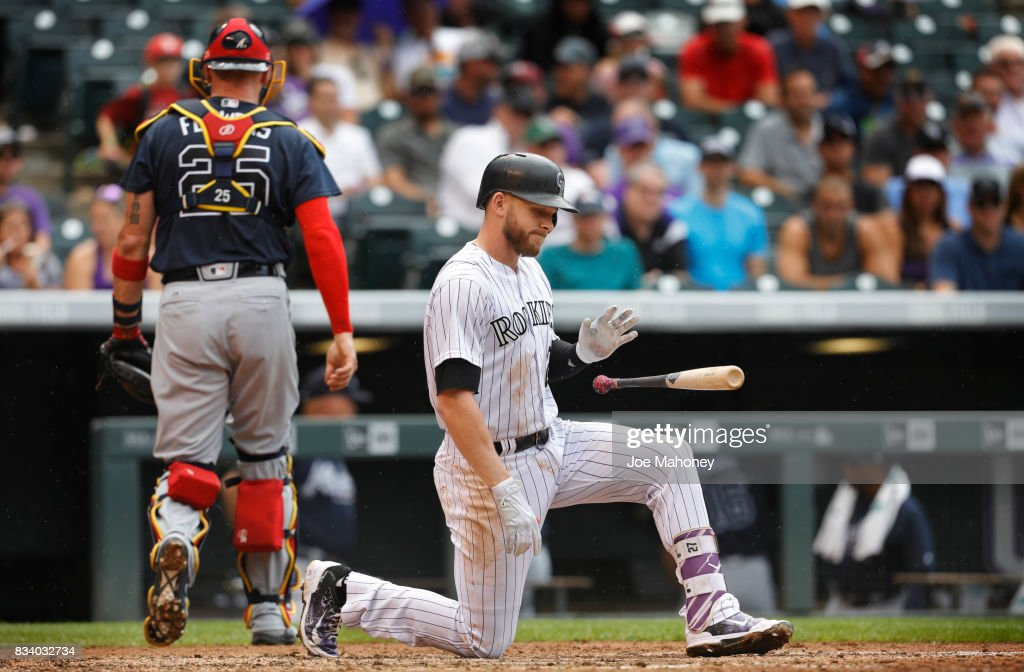 Tyler Flowers (25) of the Atlanta Braves walks to the dugout while Trevor Story (27) of the Colorado Rockies kneels at home plate and flips his bat after striking out to end the fifth inning at Coors Field on August 17, 2017 in Denver, Colorado.