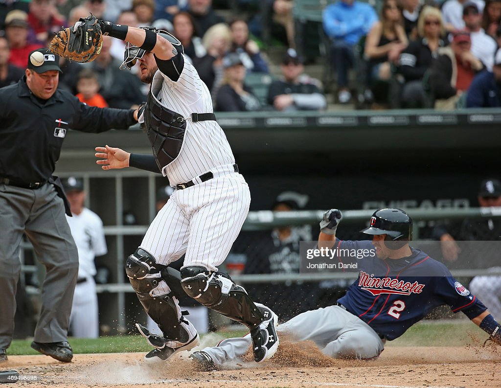 Tyler Flowers #21 of the Chicago White Sox misplays the ball as Brian Dozier #2 of the Minnesota Twins scores a run in the 8th inning at U.S. Cellular Field on April 12, 2015 in Chicago, Illinois. The White Sox defeated the Twins 6-2.