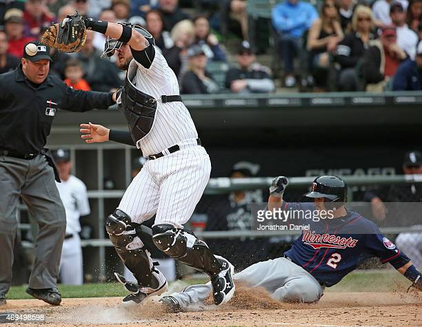 Tyler Flowers of the Chicago White Sox misplays the ball as Brian Dozier of the Minnesota Twins scores a run in the 8th inning at US Cellular Field...