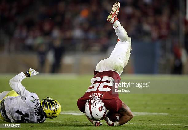 Tyler Gaffney of the Stanford Cardinal gets tripped up by Ifo EkpreOlomu of the Oregon Ducks at Stanford Stadium on November 7 2013 in Palo Alto...