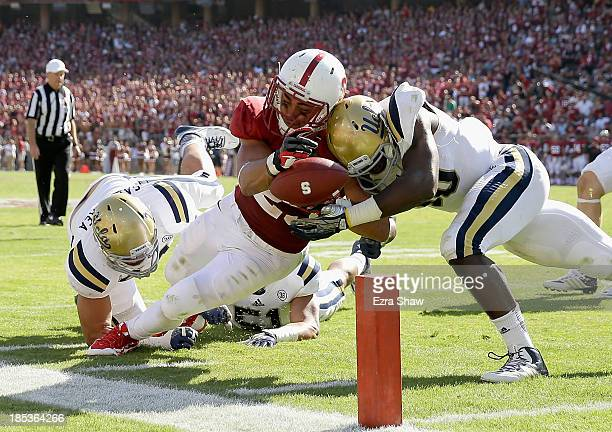 Tyler Gaffney of the Stanford Cardinal is hit by Myles Jack of the UCLA Bruins as he dives for the endzone at Stanford Stadium on October 19, 2013 in...