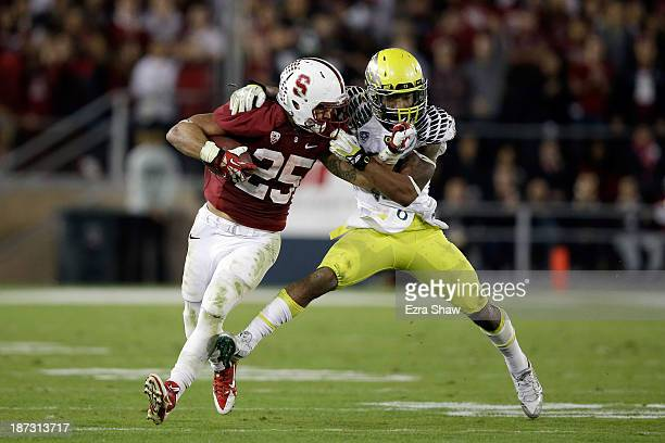 Tyler Gaffney of the Stanford Cardinal is tackled by Brian Jackson of the Oregon Ducks at Stanford Stadium on November 7 2013 in Palo Alto California...