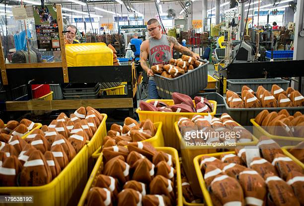 Tyler Gibson carries a tote full of turned noninflated footballs to the quality control area to be inspected at the Wilson Football Factory in Ada...