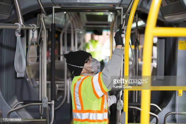 Tyler Goodwin a utility service worker for King County Metro Transit deep cleans a bus as part of its usual cleaning routine at the King County Metro...