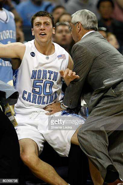 Tyler Hansbrough of the North Carolina Tar Heels goes after a loose ball into his team bench as his coach Roy Williams tries to keep him up in the...