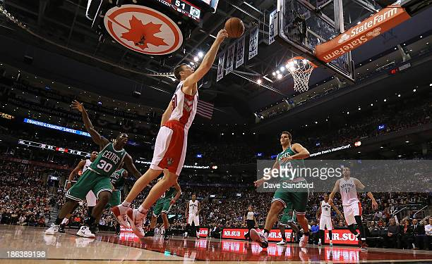 Tyler Hansbrough of the Toronto Raptors reaches for a loose ball as both Brandon Bass of the Boston Celtics and Kris Humphries of the Boston Celtics...