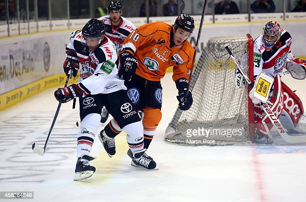 Tyler Haskins of Wolfsburg and Mirko Luedemann of Koeln battle for the puck during the DEL match between Grizzly Adams Wolfsburg and Koelner Haie at...
