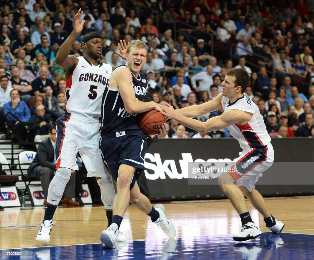 Tyler Haws #3 of the Brigham Young Cougars is fouled as he drives against Gary Bell Jr. #5 and Kevin Pangos #4 of the Gonzaga Bulldogs during the championship game of the West Coast Conference Basketball tournament at the Orleans Arena on March 11, 2014 in Las Vegas, Nevada. Gonzaga won 75-64.