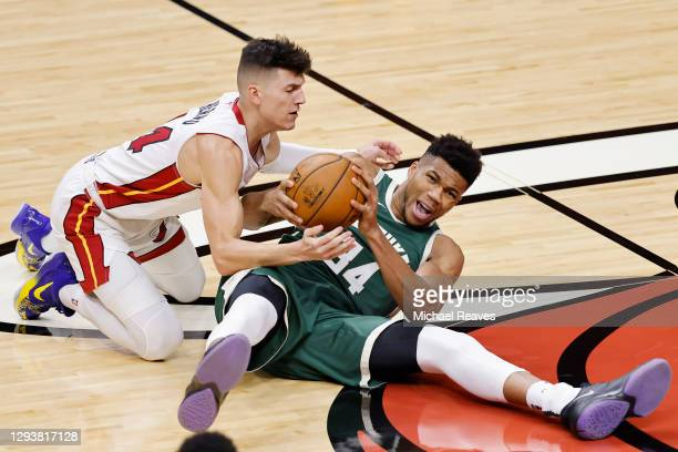 Tyler Herro of the Miami Heat and Giannis Antetokounmpo of the Milwaukee Bucks battle for control of a loose ball during the first quarter at...