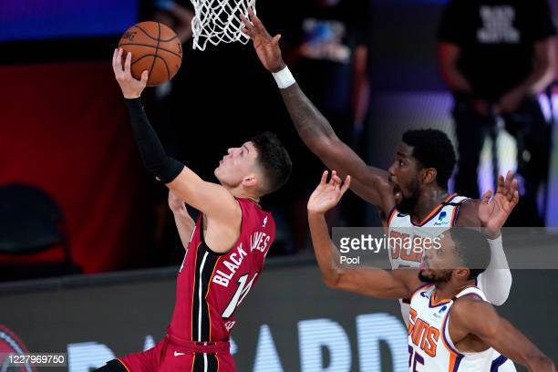 Tyler Herro of the Miami Heat drives to the basket against Deandre Ayton and Mikal Bridges of the Phoenix Suns during the second half of an NBA game...