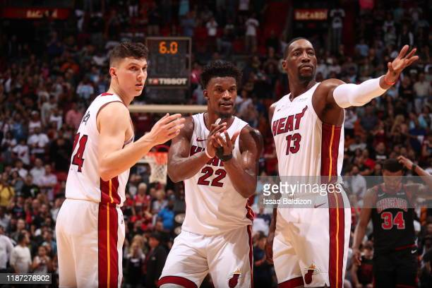 Tyler Herro of the Miami Heat Jimmy Butler of the Miami Heat and Bam Adebayo of the Miami Heat look on during a game against the Chicago Bulls on...