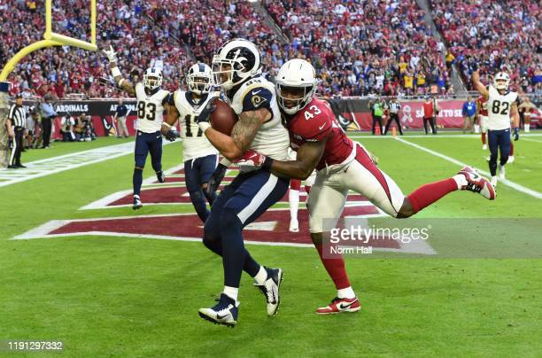 Tyler Higbee of the Los Angeles Rams catches a touchdown pass while being defended by Haason Reddick of the Arizona Cardinals in the second quarter...