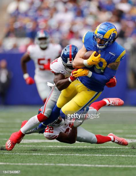 Tyler Higbee of the Los Angeles Rams is tackled by Jabrill Peppers and Adoree' Jackson of the New York Giants during the first half at MetLife...