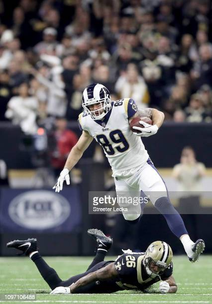 Tyler Higbee of the Los Angeles Rams jumps over P.J. Williams of the New Orleans Saints during the second quarter in the NFC Championship game at the...