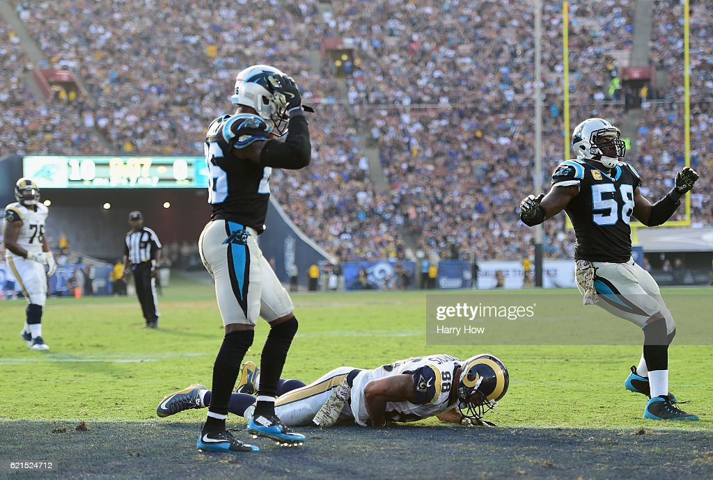 Tyler Higbee #89 of the Los Angeles Rams lies on the field after missing a catch for a touchdown between Daryl Worley #26 and Thomas Davis #58 of the Carolina Panthers during the fourth quarter of the game at the Los Angeles Coliseum on November 6, 2016 in Los Angeles, California.