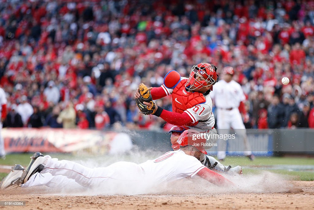 Tyler Holt #40 of the Cincinnati Reds slides home with the tying run ahead of the throw to Carlos Ruiz #51 of the Philadelphia Phillies after a sacrifice fly by Zack Cozart in the eighth inning of the opening day game at Great American Ball Park on April 4, 2016 in Cincinnati, Ohio. The Reds defeated the Phillies 6-2.