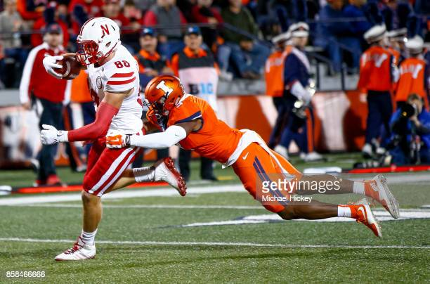 Tyler Hoppes of the Nebraska Cornhuskers runs the ball for a touchdown as Del'Shawn Phillips of the Illinois Fighting Illini tries to make the stop...