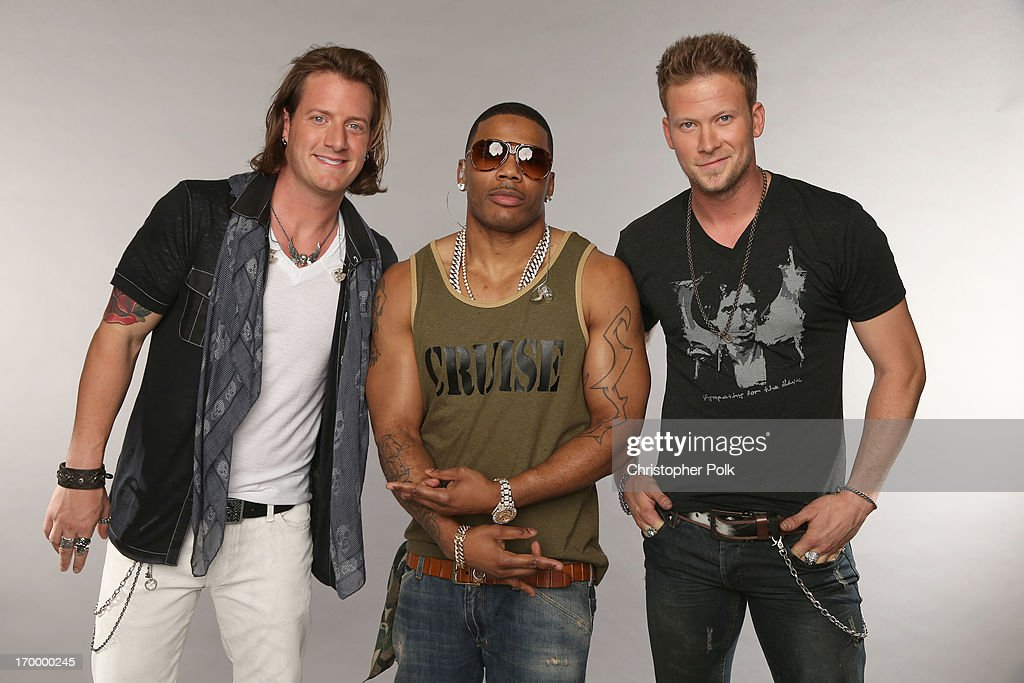 Tyler Hubbard and Brian Kelley of Florida Georgia Line pose with Nelly (C) at the Wonderwall portrait studio during the 2013 CMT Music Awards at Bridgestone Arena on June 5, 2013 in Nashville, Tennessee.