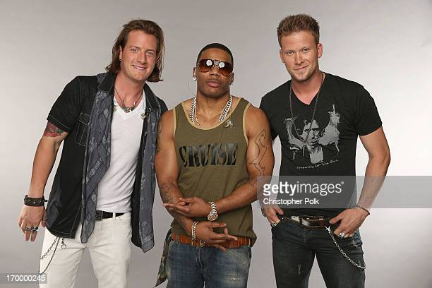 Tyler Hubbard and Brian Kelley of Florida Georgia Line pose with Nelly at the Wonderwall portrait studio during the 2013 CMT Music Awards at...