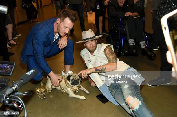 Tyler Hubbard and Brian Kelley of musical group Florida Georgia Line take photos with Doug The Pug at the 2018 CMT Music Awards Backstage Audience at...
