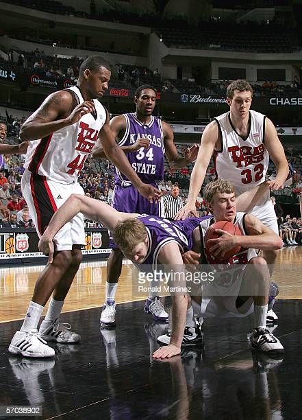 Tyler Hughes of the Kansas State Wildcats falls over Alan Voskuil of the Texas Tech Red Raiders as Voskuil holds on to the ball during the first...