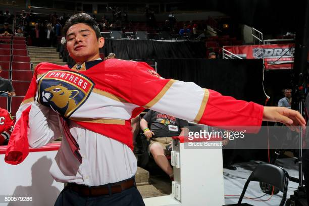 Tyler Inamoto puts on the Florida Panthers jersey after being selected 133rd overall during the 2017 NHL Draft at the United Center on June 24 2017...