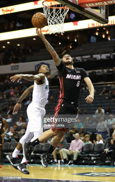 Tyler Johnson of the Miami Heat drives to the basket against Malik Monk of the Charlotte Hornets during their game at Spectrum Center on October 2...