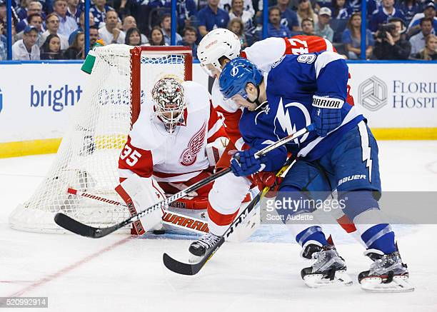 Tyler Johnson of the Tampa Bay Lightning battles for the puck against goalie Jimmy Howard and Alexei Marchenko of the Detroit Red Wings during the...