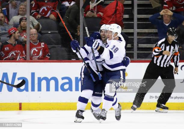 Tyler Johnson of the Tampa Bay Lightning celebrates his game winning goal in overtime against the New Jersey Devils and is joined by Ondrej Palat at...