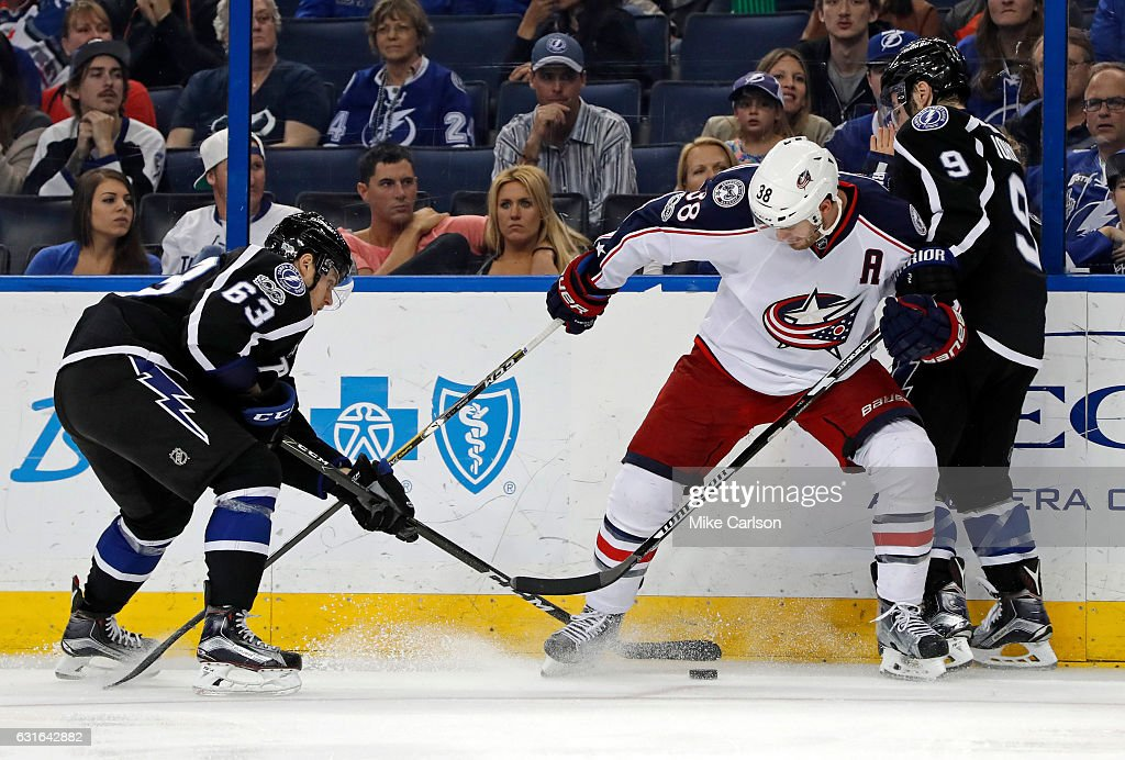 Tyler Johnson #9 of the Tampa Bay Lightning holds Boone Jenner #38 of the Columbus Blue Jackets as Matthew Peca #63 reaches for the puck at the Amalie Arena on January 13, 2017 in Tampa, Florida.