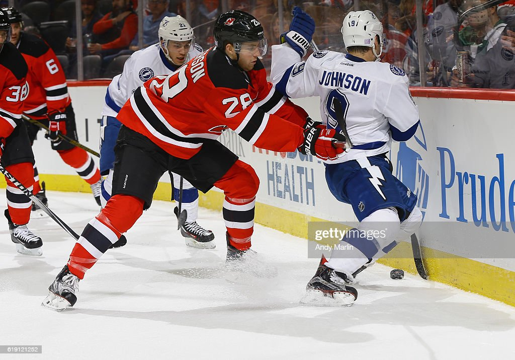 Tyler Johnson #9 of the Tampa Bay Lightning is checked by Damon Severson #28 of the New Jersey Devils during the game at Prudential Center on October 29, 2016 in Newark, New Jersey.