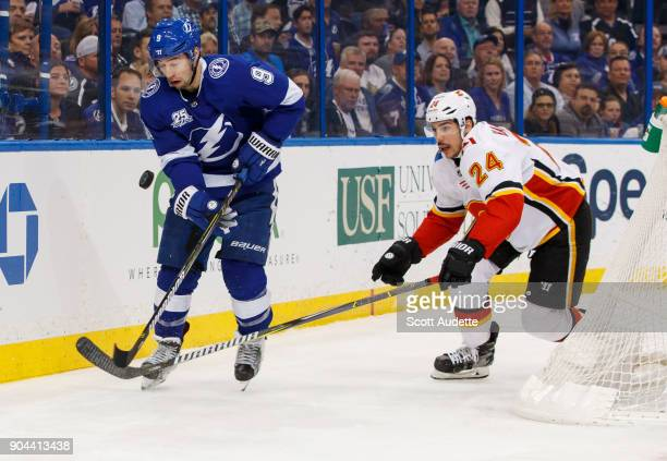 Tyler Johnson of the Tampa Bay Lightning skates against Travis Hamonic of the Calgary Flames during the first period at Amalie Arena on January 11...