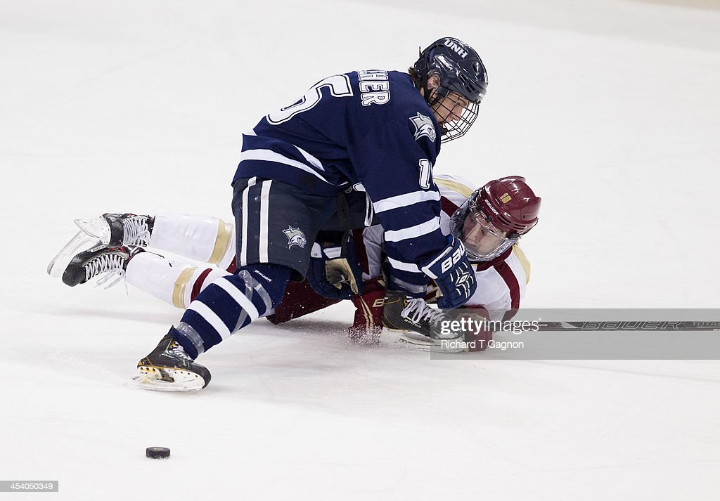 Tyler Kelleher #16 of the New Hampshire Wildcats falls on Michael Sit #18 of the Boston College Eagles during NCAA hockey action at Kelley Rink on December 6, 2013 in Chestnut Hill, Massachusetts.
