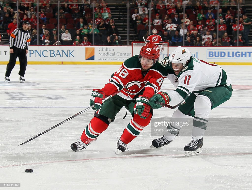 Tyler Kennedy #48 of the New Jersey Devils is checked by Zach Parise #11 of the Minnesota Wild at the Prudential Center on March 17, 2016 in Newark, New Jersey. The Devils defeated the Wild 7-4.