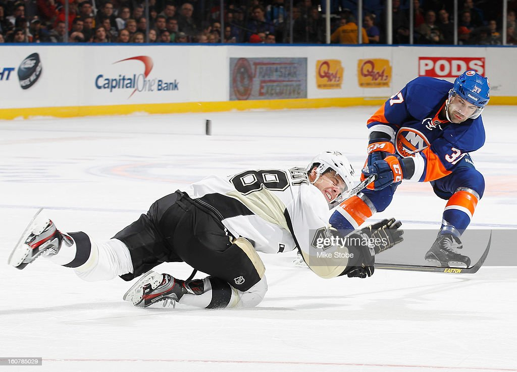 Tyler Kennedy #48 of the Pittsburgh Penguins is tripped up in front of Brian Strait #37 of the New York Islanders at Nassau Veterans Memorial Coliseum on February 5, 2013 in Uniondale, New York. The Penguins defeated the Islanders 4-2.