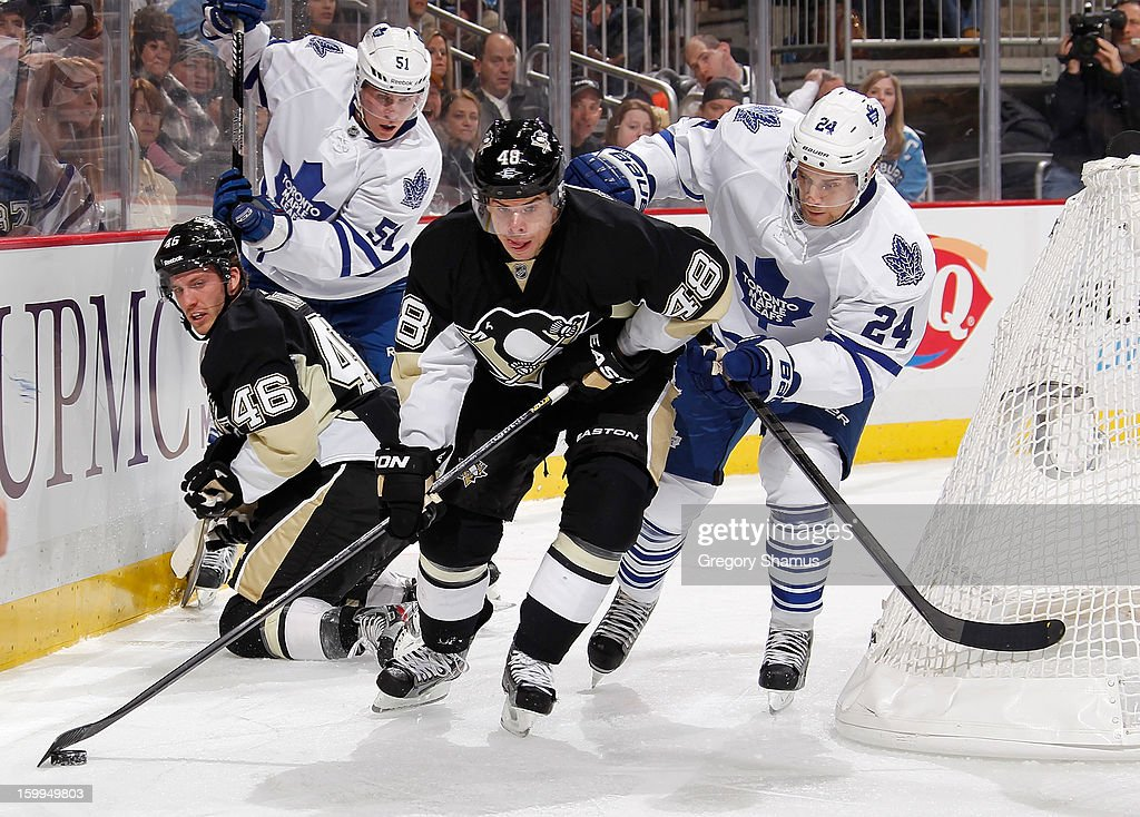 Tyler Kennedy #48 of the Pittsburgh Penguins moves the puck in front of John-Michael Liles #24 of the Toronto Maple Leafs on January 23, 2013 at Consol Energy Center in Pittsburgh, Pennsylvania. Toronto won the game 5-2.