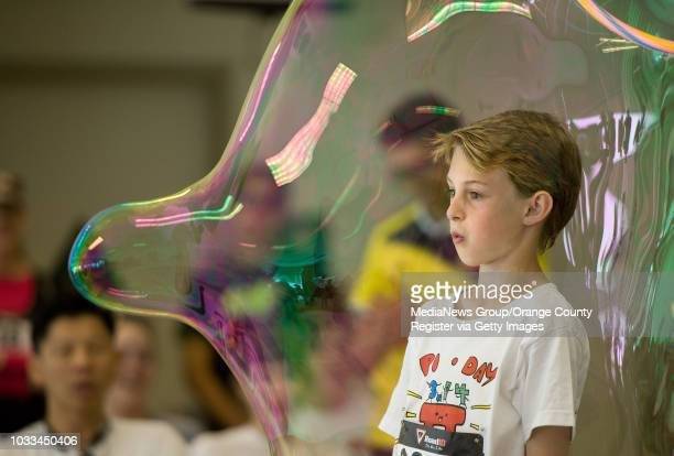 Tyler Kokes looks out from a bubble during a demonstration on the science of bubbles at Edison High School on Saturday during a Pi Day celebration of...