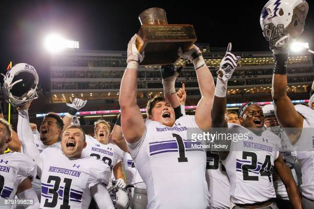 Tyler Lancaster of the Northwestern Wildcats hoists the Land of Lincoln Trophy after defeating the Illinois Fighting Illini 427 at Memorial Stadium...
