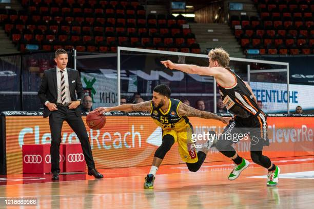 Tyler Larson, No. 55 of Oldenburg and Per Guenther, No. 06 of Ulm fight for the ball next to Jaka Lakovic, head coach of Ulm, during the EasyCredit...