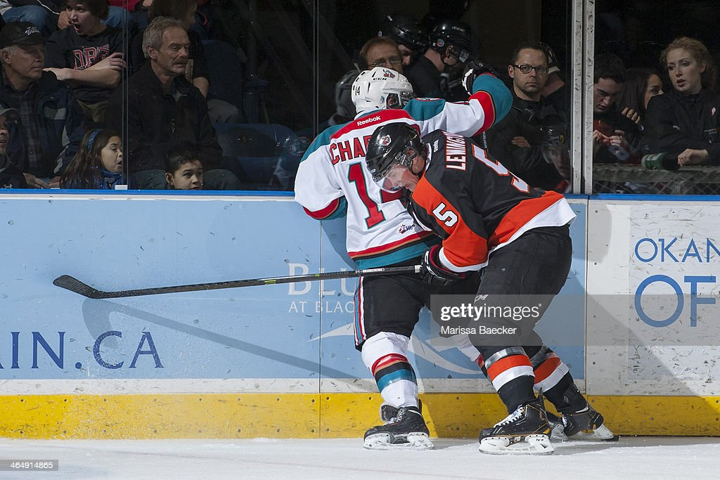 Tyler Lewington #5 of the Medicine Hat Tigers checks Rourke Chartier #14 of the Kelowna Rockets into the boards on January 24, 2014 at Prospera Place in Kelowna, British Columbia, Canada.