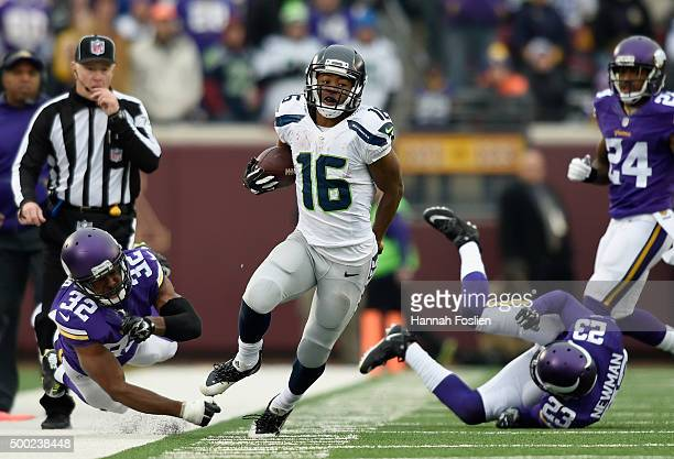 Tyler Lockett of the Seattle Seahawks avoids tackles by Antone Exum and Terence Newman of the Minnesota Vikings during the fourth quarter of the game...