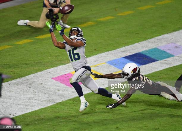Tyler Lockett of the Seattle Seahawks catches a touchdown pass while being defended by Dre Kirkpatrick of the Arizona Cardinals during the fourth...