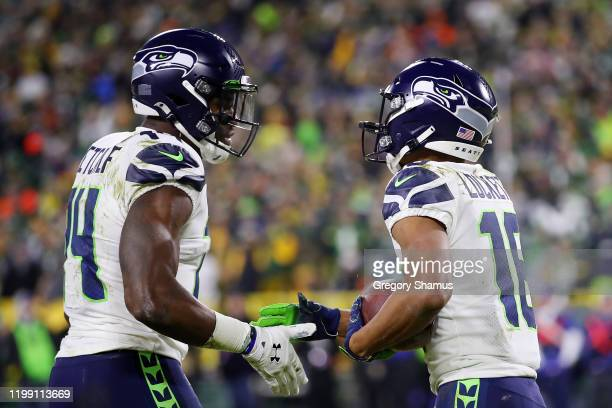Tyler Lockett of the Seattle Seahawks celebrates with DK Metcalf after scoring a touchdown during the third quarter against the Green Bay Packers in...