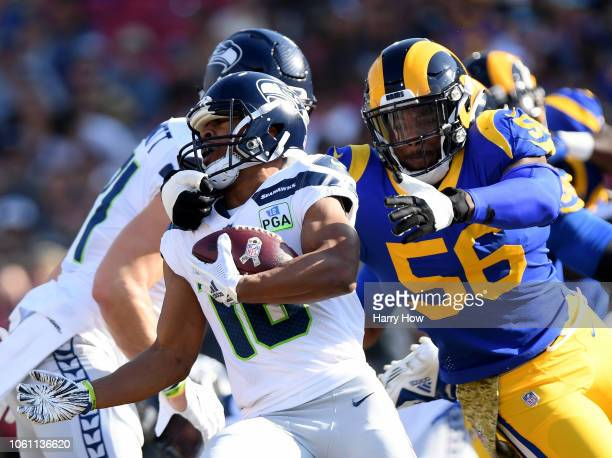 Tyler Lockett of the Seattle Seahawks is grabbed by Dante Fowler of the Los Angeles Rams during a 3631 Rams win at Los Angeles Memorial Coliseum on...